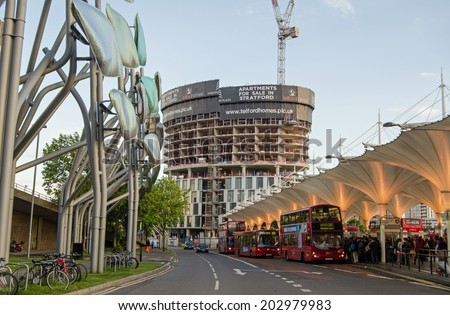 LONDON, ENGLAND - MAY 13, 2014: Passengers getting on buses in the early evening at Stratford in East London.  The town is a busy transport hub in the area. - stock photo