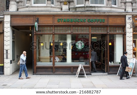 London, England - Sept 11, 2014: People passing by and entering a Starbucks store in Central London, England. Starbucks has outlets in more than 50 countries worldwide. - stock photo