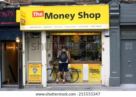 London, England - Sept 4th, 2014: A man stands at the window of The Money Shop in the Soho area of London. The Money Shop provides payday loans, pawn brokering and other financial services in the UK - stock photo