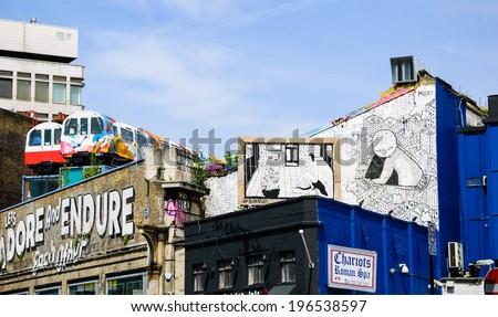 LONDON, ENGLAND, UK - MAY 4, 2014: Black and white graffiti (created by MIIIO and NoBearWalls) on Village Underground wall. Urban art in this area attracts tourists from all over the world. - stock photo