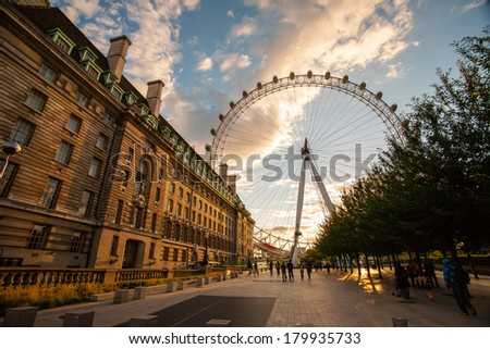 London Eye at dusk in London/London Eye at dusk in London/London, UK - July 21 : Tourists walk towards at sunset with golden light covering the London Eye on July 21 2008. - stock photo