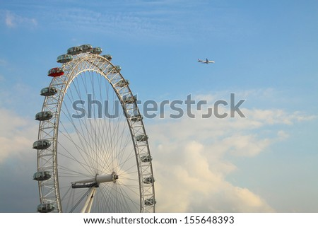 London eye with airplane and clouds - stock photo