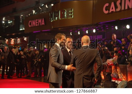 LONDON -  FEBRUARY 7:  Actor Bruce Willis and Sebastian Koch and Jai Courtney are posing on the Red Carpet Premiere of A Good Day To Die Hard in London, UK on Thursday,  February 7, 2013. - stock photo