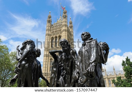 LONDON, GREATER LONDON, ENGLAND - JUNE 30: Les Bourgeois de Calais sculpture by Auguste Rodin  completed in 1889 and Victoria Tower on June 30, 2012 in London, Greater London, England. - stock photo