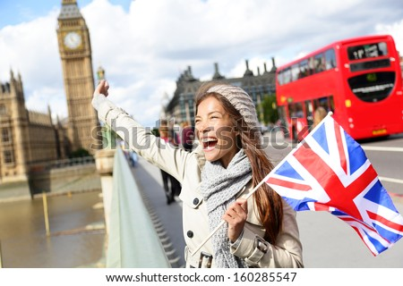 London - happy tourist holding British UK flag by Big Ben and red double decker bus. Excited girl sightseeing travel on Westminster Bridge, London, England, United Kingdom. Multiracial Asian Caucasian - stock photo