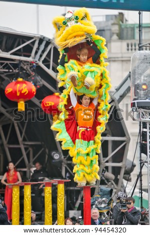 LONDON, JANUARY 29: The Chen brothers perform a traditional Flying Lion dance at the Chinese New Year celebrations in Trafalgar Square on January 29, 2012 in London. - stock photo