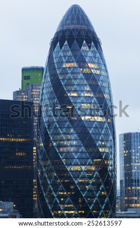 LONDON - JANUARY 18, 2015.  The modern glass buildings of the Swiss Re Building or informally the Gherkin. This tower is 180 meters tall and stands in the City of London Financial District. - stock photo