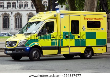 LONDON - JUL 1, 2015: Emergency Ambulance speeds along a street in London in response to an emergency call. - stock photo