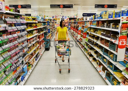 LONDON - JUN 14: A shopper browses an aisle at a Sainsbury's supermarket on Jun 14, 2014 in London, UK. Sainsbury's is the UK's second largest supermarket with a revenue of £23 billion in 2013. - stock photo