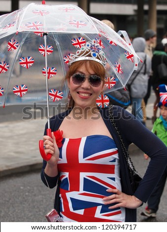LONDON - JUNE 3: A happy unidentified girl with Union Jack dress on the River Thames to witness Thames Diamond Jubilee Pageant on June 3, 2012 in London. - stock photo