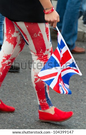 LONDON - JUNE 5:  A young woman wears Union Jack trousers and holds a flag as she walks towards Buckingham Palace during the Diamond Jubilee celebrations on June 5, 2012 in London. - stock photo