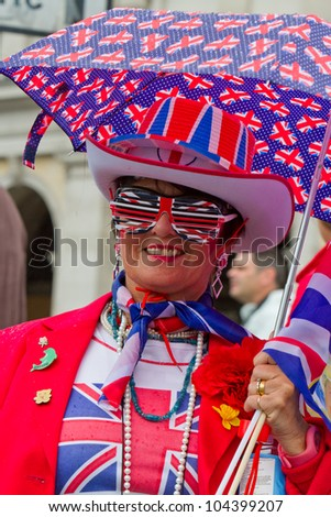 LONDON - JUNE 5: An unidentified woman dressed in red, white and blue, holding umbrella celebrates Diamond Jubilee celebrations on June 5, 2012 in London. - stock photo