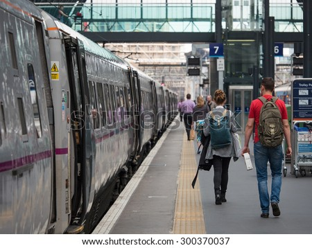 LONDON - JUNE 17, 2015: People walking inside King's Cross railway station, a major London railway terminus which opened in 1852 on the northern edge of central London. - stock photo