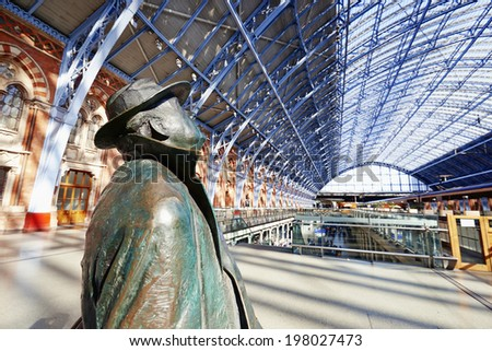 LONDON - JUNE 8. Standing in the restored and redeveloped St Pancras International rail station is a statue of Sir John Betjeman who saved the building from demolition; June 8, 2014 in London, UK. - stock photo