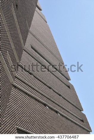 LONDON - JUNE 6, 2016. The angular perforated brickwork of the Tate Modern art gallery extension designed by Herzog & de Meuron filters daylight in and emits artificial light at Bankside, London. - stock photo