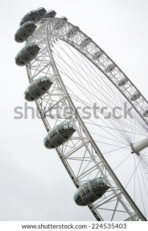 LONDON - JUNE 25: The London Eye Ferris wheel pictured on June 25, 2014, in London, UK. It is the tallest Ferris wheel in Europe, and the most popular paid tourist attraction in the United Kingdom. - stock photo