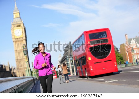 London lifestyle woman running near Big Ben. Female runner jogging training in city with red double decker bus. Fitness girl smiling happy on Westminster Bridge, London, England, United Kingdom. - stock photo