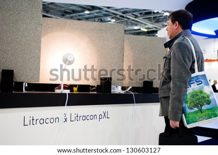 LONDON - MAR 6: a visitor looks at new Litracon panels during Ecobuild 2013 in London, UK on March 6, 2013. - stock photo