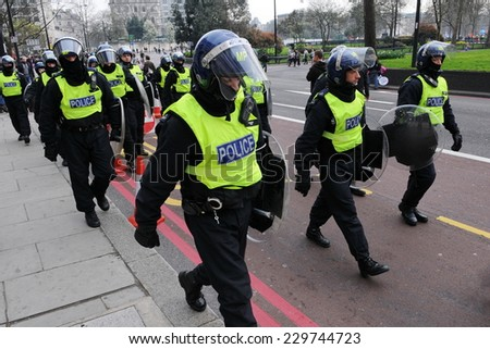 LONDON - MAR 26: Police in riot gear deploy on a city street after violent clashes with anti-cuts demonstrators on Mar 26, 2011 in London, UK. An estimated 250,000 rallied against government cuts. - stock photo