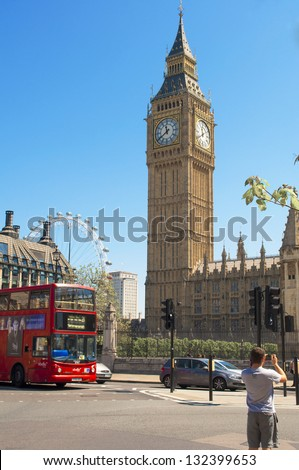 LONDON, MAR. 20: Typical red double-decker bus that passes in front of Big Ben in London on March 20, 2013. Both the red double-decker bus and Big Ben are symbols of London. - stock photo