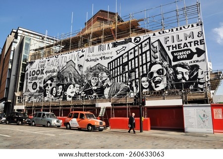 LONDON -  MARCH 7, 2015. A giant mural by artist Gregori Saavedra wraps the 1865 German Gymnasium now under transformation into a complex of restaurants at King's Cross, London, UK. - stock photo