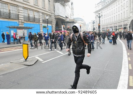 LONDON - MARCH 26: A protester runs along Regent Street during a large anti-cuts rally on March 26, 2011 in London, UK. An estimated 250,000 people took part in the TUC organised rally. - stock photo