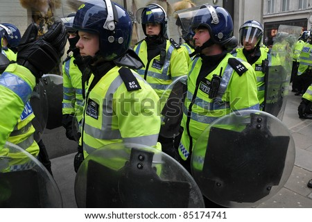 LONDON - MARCH 26: Police in riot gear on standby in central London during a large anti-cuts rally on March 26, 2011 in London, UK. - stock photo