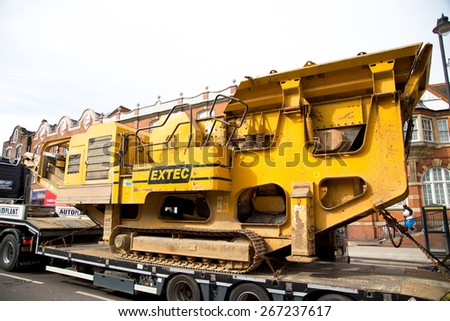 LONDON - MARCH 30TH: A transporter  carries a rock crushing machine on March the 30th, 2015, in London, England, UK. Rock crushers are widely used in construction and mining industries. - stock photo