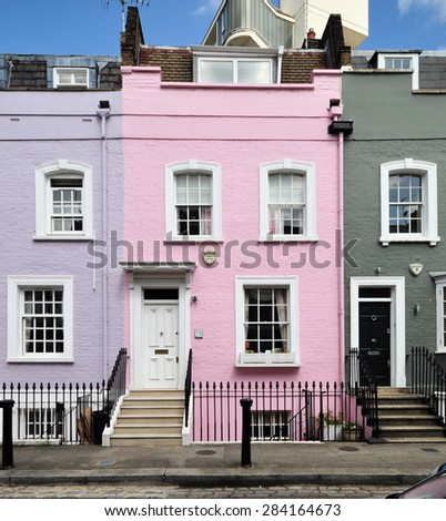 LONDON - MAY 26, 2015. A pink painted facade in a terrace of small eighteenth century English Georgian period town houses at Bywater Street in the Royal Borough of Kensington and Chelsea, London, UK - stock photo