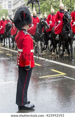 LONDON - MAY 18, 2016: Guard stands at attention as a horse-drawn procession carrying Queen Elizabeth II toward Buckingham Palace passes along a rainy street.   - stock photo