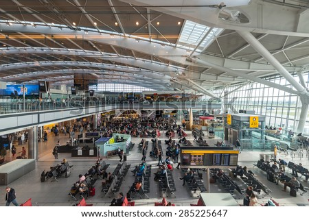 LONDON - MAY 21, 2015: People walking inside terminal of Heathrow Airport, the busiest airport in the United Kingdom and the busiest airport in Europe by passenger traffic. - stock photo