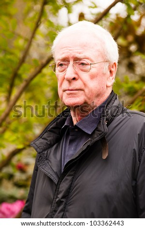 LONDON - MAY 21: Sir Michael Caine at the RHS Chelsea Flower Show in London on May 21, 2012. He is a famous english actor, knighted by Queen Elizabeth II in recognition of his contribution to cinema - stock photo