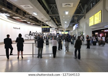 LONDON - MAY 13: Travelers arrive at Heathrow airport on May 13, 2012 in London, England. Heathrow has been world's busiest airports by international passenger traffic since 2000 (64.7 million in 2011). - stock photo