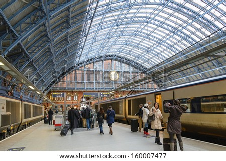 LONDON - MAY 15: Travelers hurry on May 15, 2013 at St. Pancras train station in London. With 26 million annual travelers (2011-12) it is one of the busiest stations in the UK. - stock photo
