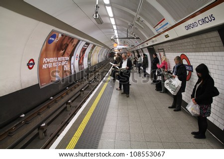 LONDON - MAY 14: Travelers wait at Oxford Circus underground station on May 14, 2012 in London. London Underground is the 11th busiest metro system worldwide with 1.1 billion annual rides. - stock photo