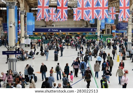 LONDON - MAY 30: Travellers walk through Victoria train station on May 30, 2015 in London, UK. Victoria is the second busiest train station in the UK with 73 million passengers entry and exits.  - stock photo