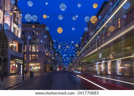 LONDON - NOVEMBER 21st 2015: Christmas lights on Oxford Street, London, UK. The full length of the busiest shopping area in central London is decorated with 1778 glowing white and golden orbs. - stock photo