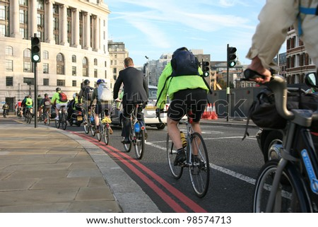 LONDON - OCT 7: Commuters on rental bike on Oct 7, 2010 in London, UK. London's bicycle sharing scheme, launched with 6000 bikes, 400 docking stations on 2010 to help ease traffic congestion. - stock photo