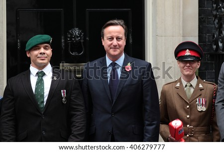LONDON - OCT 22, 2015: Prime Minister David Cameron buys his remembrance poppy from Corporal Linda for this years Poppy appeal at 10 Downing Street on Oct 22, 2015 London - stock photo