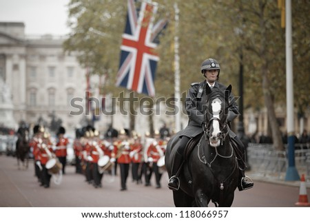 LONDON - OCTOBER 25: Policewoman on the horse behind marching the Queen's Guards during traditional Changing of the Guards ceremony at Buckingham Palace on October 25, 2012 in London, United Kingdom. - stock photo