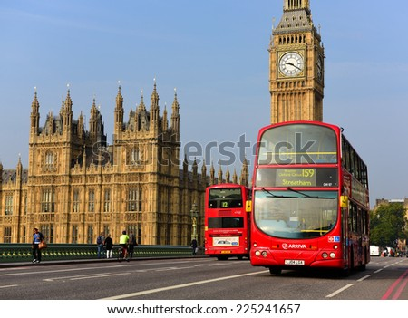 LONDON - SEP 22: A London red bus near Big Ben on September 22, 2014 in London. The London Bus service is one of the largest urban bus networks in the world with 8,000 buses covering 700 routes. - stock photo