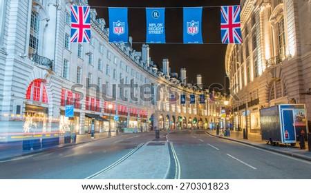 LONDON - SEPTEMBER 28, 2013: Tourists walk along Regent Street at night. More than 40 million people visit London annually. - stock photo