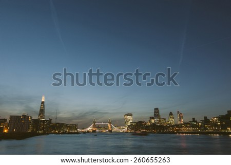 London skyline at dusk with River Thames on foreground. From left to right The Shard, Tower Bridge, Walkie Talkie and other skyscrapers. All buildings have lights on. - stock photo
