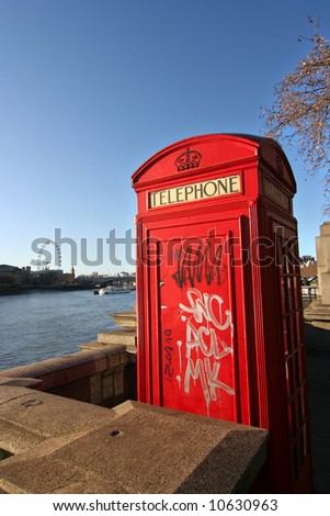 London telephone booth along the Thames, sprayed with graffiti - stock photo