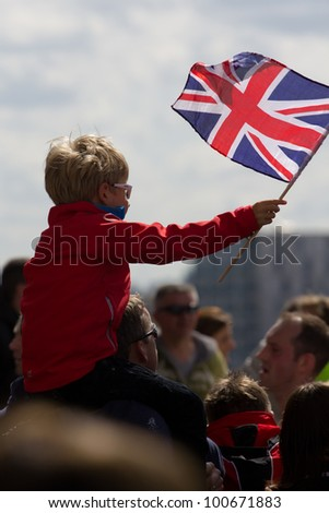 LONDON, UK - APR. 22: A boy waves a union jack flag as tens of thousands of people pass Tower Bridge during the London Marathon on the Apr 22, 2012 in London, UK - stock photo