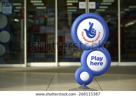 LONDON, UK - APRIL 07: Blue National lottery sign in front of shop, showing its crossed fingers logo. On 07 April 2015. - stock photo
