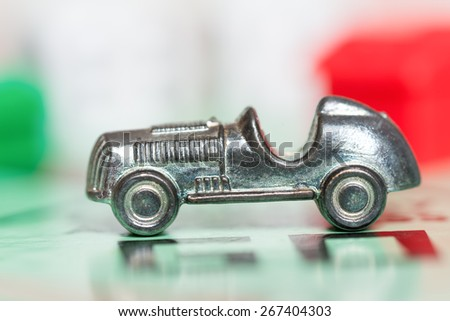 LONDON,UK - APRIL 1,2015 : Car token at the GO space of a monopoly game board - stock photo