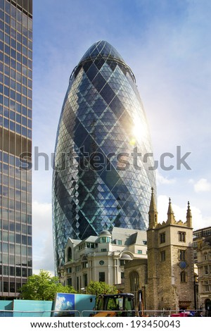 LONDON, UK - APRIL 24, 2014: Gherkin building glass windows texture reflects the sky buildings of the Swiss Re Gherkin, is 180 meters tall, stands in the City of London - stock photo