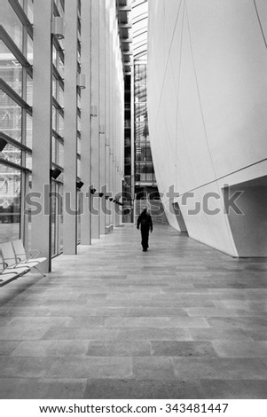 LONDON, UK - APRIL 28 2013: Man walking down the hallway in the Darwin Center at the Natural History Museum. With over 70 million specimens on display it's one of Londons most popular attractions. - stock photo