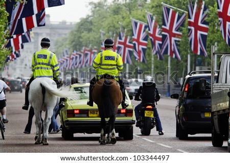 LONDON, UK - APRIL 28, 2011: Mounted policemen on the Mall which is decorated with Union Jack flags in preparation of the Royal Wedding to be held the day after on April 28, 2011 in London. - stock photo